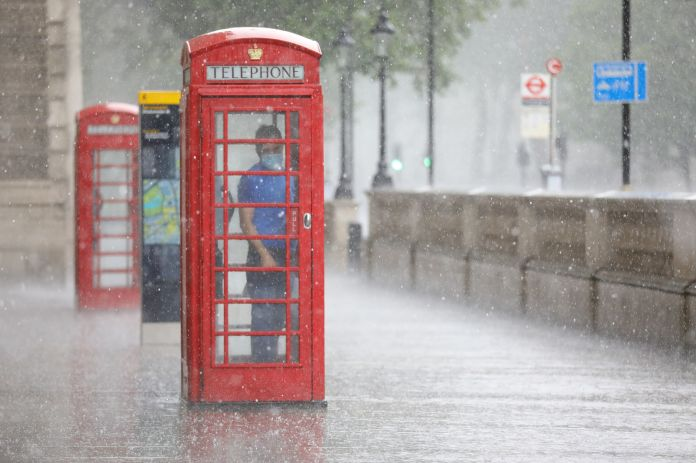 A man takes shelter from the downpour in a telephone booth