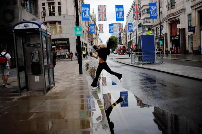 A pedestrian jumps through large puddles in London after being caught in a downpour of rain on Oxford Street
