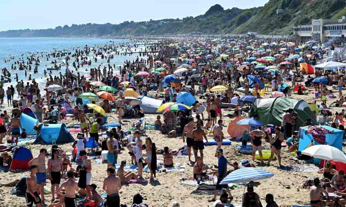 Britons soak up the sun by sunbathing and playing in the sea on Bournemouth Beach