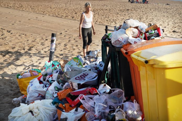 Garbage cans overflowing with beer cans and plastic bags Tynemouth Beach