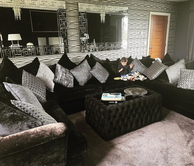 The living room features a huge velvet black sofa with silver and grey cushions