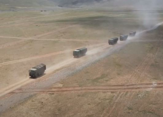 Chinese military trucks move through the landscape