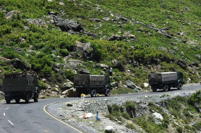 A convoy of Indian trucks is seen driving through the mountains to the border