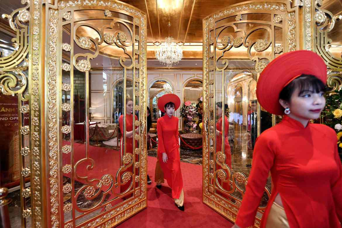 Hotel staff welcome guests through the lobby's golden gates