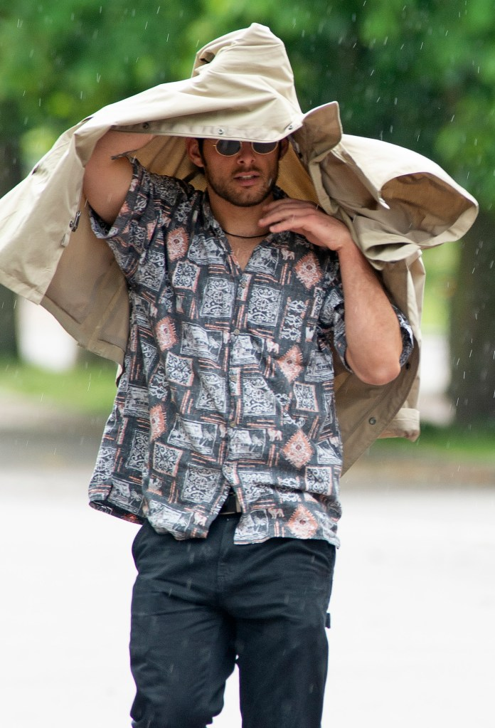 Man uses his jacket to protect himself from wind and rain