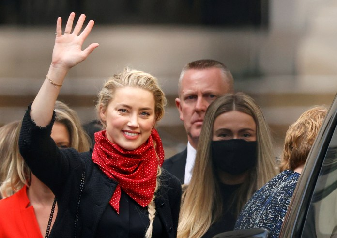 Amber Heard smiles as he leaves the High Court