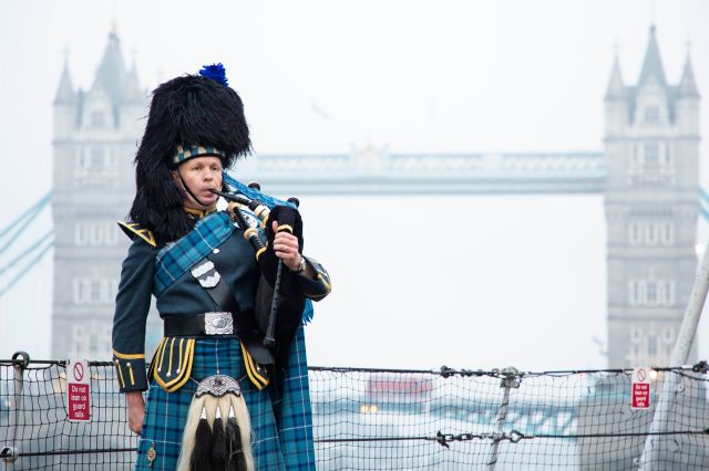 Pipe Sergeant Neil Esslemont of RAF Halton Pipes & Drums in front of Tower Bridge in London on the 75th anniversary of VJ Day