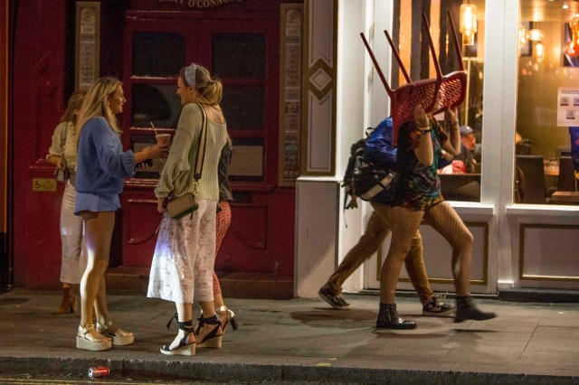 Revellers carry a chair through the streets of London's Soho
