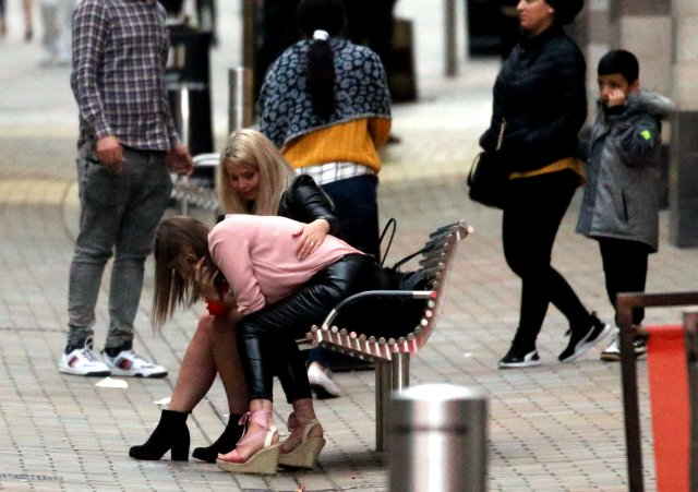 One girl was pictured doubled over on a bench in daylight as her friend rubbed her back and families walked past
