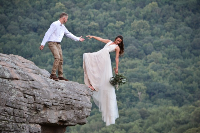 The daring couple posed on the edge of the immense cliff