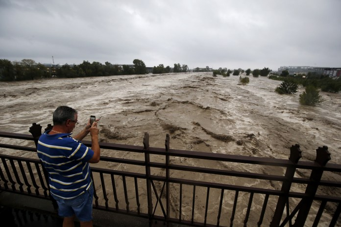 A man takes a photo of the Var flooded in the Nice region during storm Alex last night