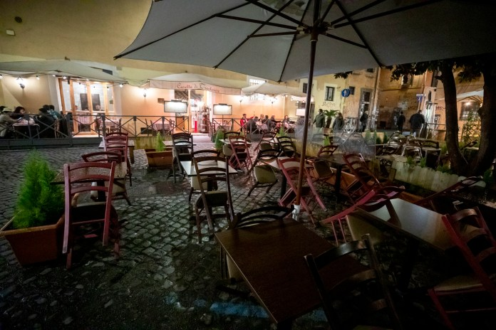 The Italian government has refused to rule out the closure of cities like Rome (an empty restaurant in the capital is shown)