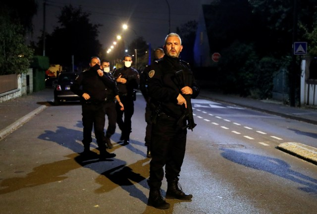 Armed cops stand guard on Friday night in the French suburb