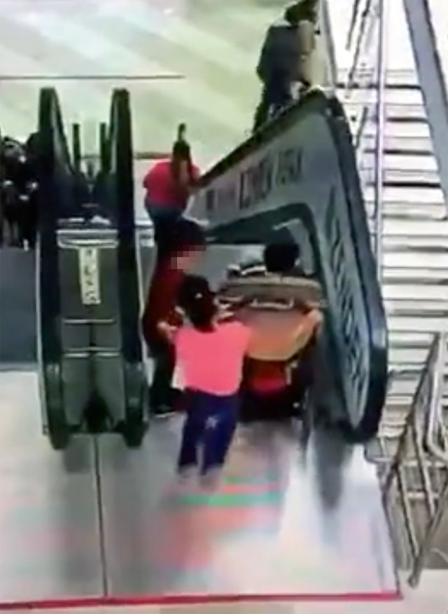 The children attempt to move the pushchair onto the escalator