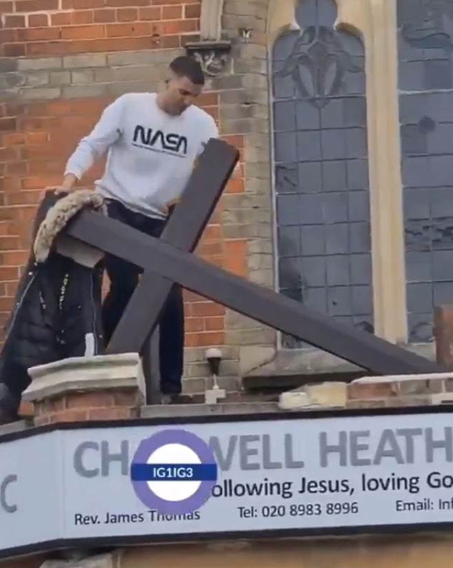 Moment vandal is filmed trying to rip cross from roof of church in east London as cops arrest suspect