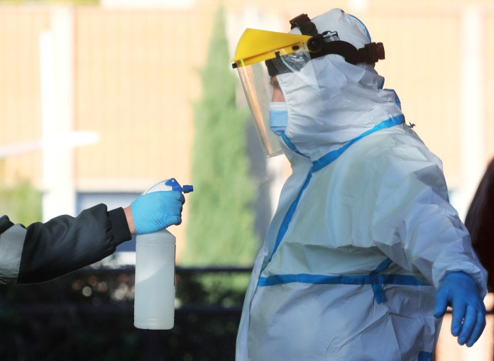 A paramedic wearing full personal protective equipment (PPE) is disinfected in Madrid, Spain