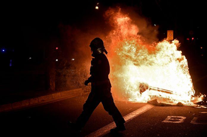 Firefighter walks past burning trash can during Barcelona protests