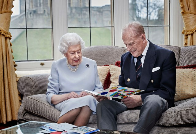 The Queen and Prince Philip open an anniversary card from great-grandchildren Prince George, Princess Charlotte and Prince Louis