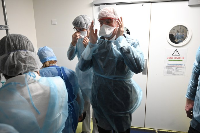 French Prime Minister Castrex wearing protective gear during his visit to an intensive care unit in Saint-Etienne