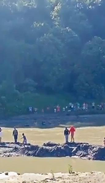 Les résidents regardent les sauveteurs essayer de récupérer l'homme de la rivière