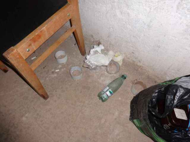 Used rolls of tape and bottled water can be seen on the floor