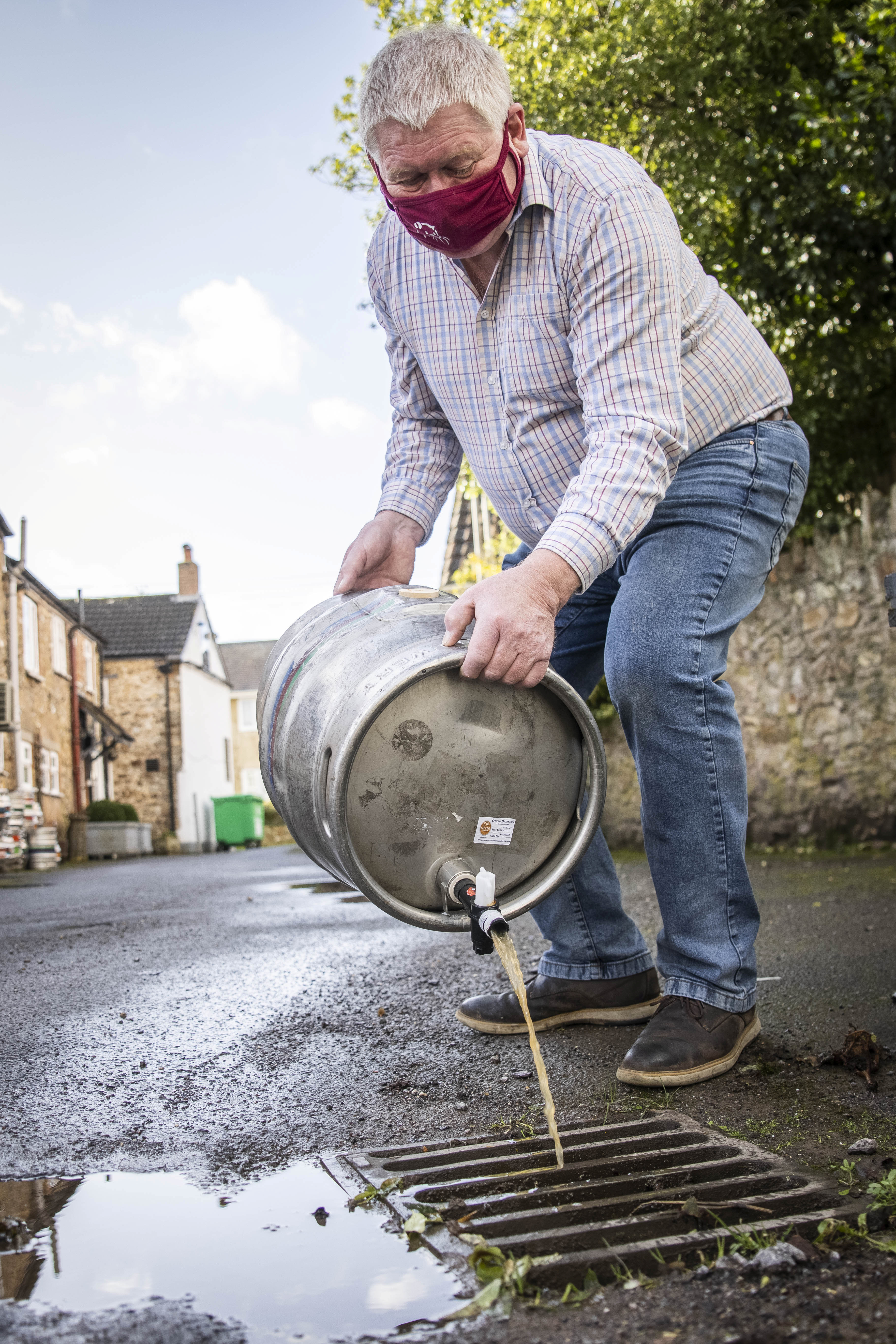 Patrick Mahoney, landlord of The Winchester Arms, pours out-of-date beer down the drain in Taunton, February 18 2021