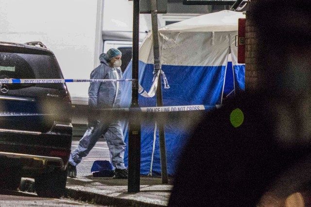 Forensics officers are seen at the crime scene after following the fatal stabbing on West Green Road