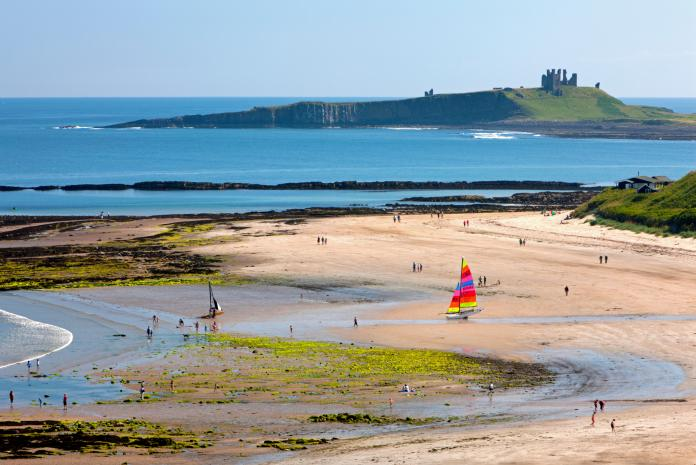 The beach is overlooked by Dunstanburgh Castle