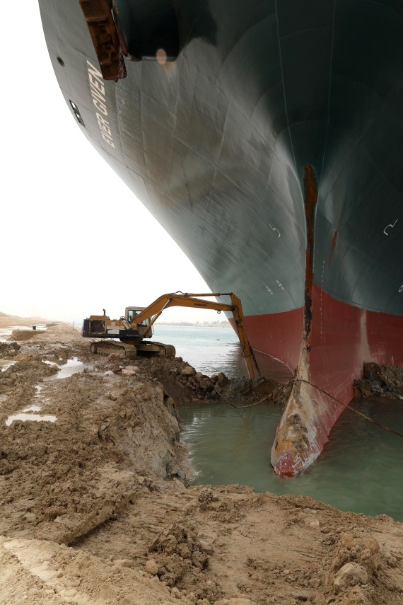 The lone digger struggles to clear sand from the Ever Given embedded in the bank of the Suez Canal
