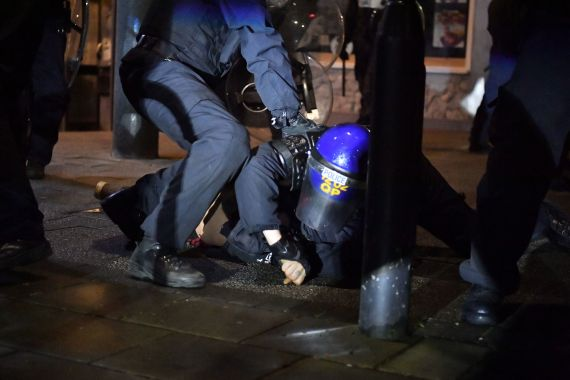 Police officers detain a man as they move in on demonstrators in Bristol