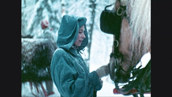 A young Queen pets the horses on the horsedrawn sleigh ride in Canada