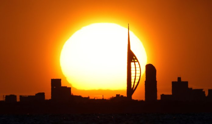 Sunrise over the Spinnaker Tower in Portsmouth pictured from across The Solent on a bright sunny morning