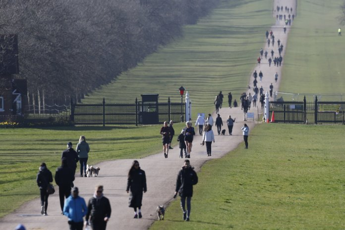 People walk and run on The Long Walk leading to Windsor Castle in morning sunshine