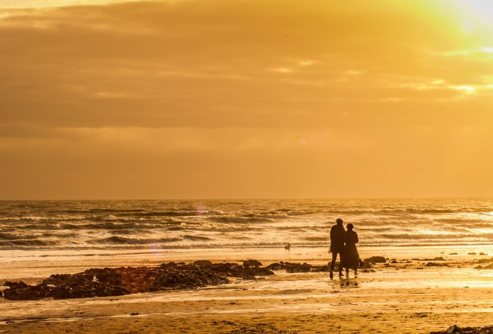 Walkers enjoy a glorious sunset last night in Eastbourne, East Sussex