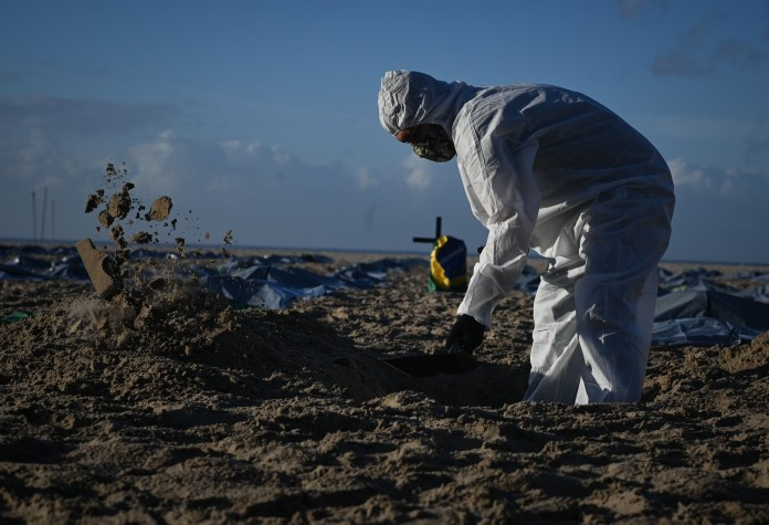 An activist from NGO Rio de Paz digs a grave wearing a biological protection suit in front of death bags during a symbolic act in protest for the memory of the 400,000