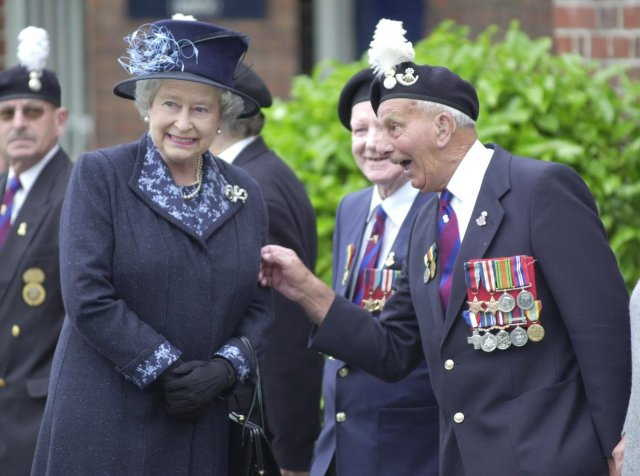 D-Day hero John Bellis gives the Queen a nudge on the arm during a visit to an Army barracks in Wrexham in 2002