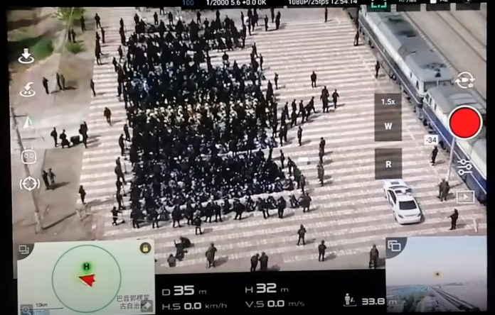 Drone footage shows Chinese police transferring hundreds of blindfolded, shackled prisoners to re-education camps