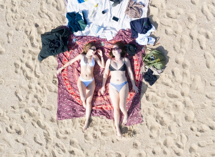 Sunbathers Karla Noren (left) and Gemima Picton, both 19, enjoy the hottest March day in 53 years at Bournemouth Beach