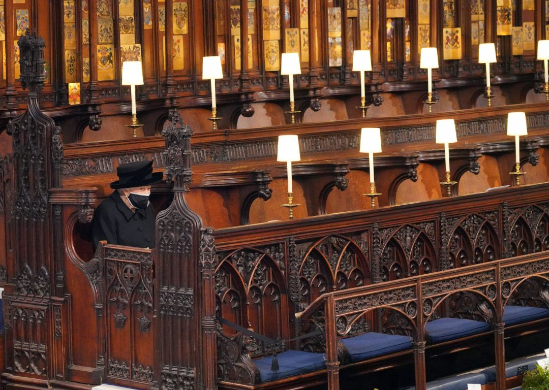 The Queen sitting alone as she looks at her husband's coffin