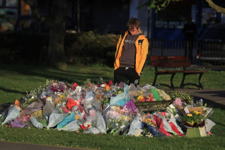 Julia's son Patrick James looks at floral tributes left near his family home