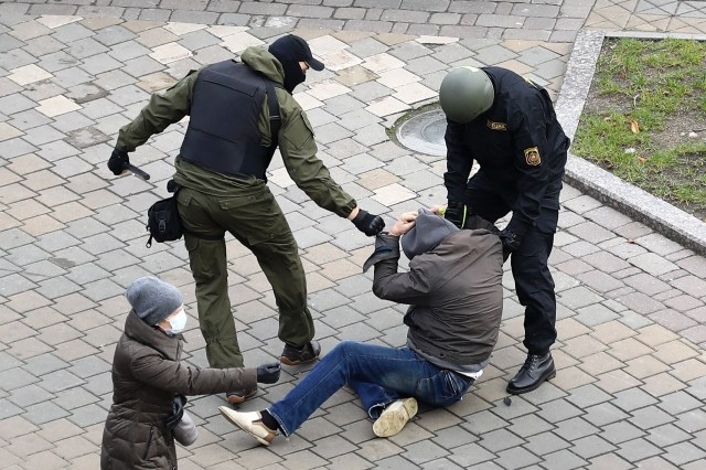 Police officers detain a man in Minsk during a demonstration against the President