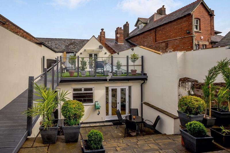 The huge outdoor space has an impressive patio that sweeps up towards a roof terrace