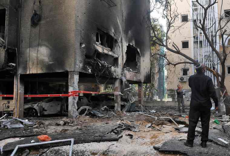 Hombres israelíes revisan los daños después de un cohete disparado desde la Franja de Gaza controlada por Hamas