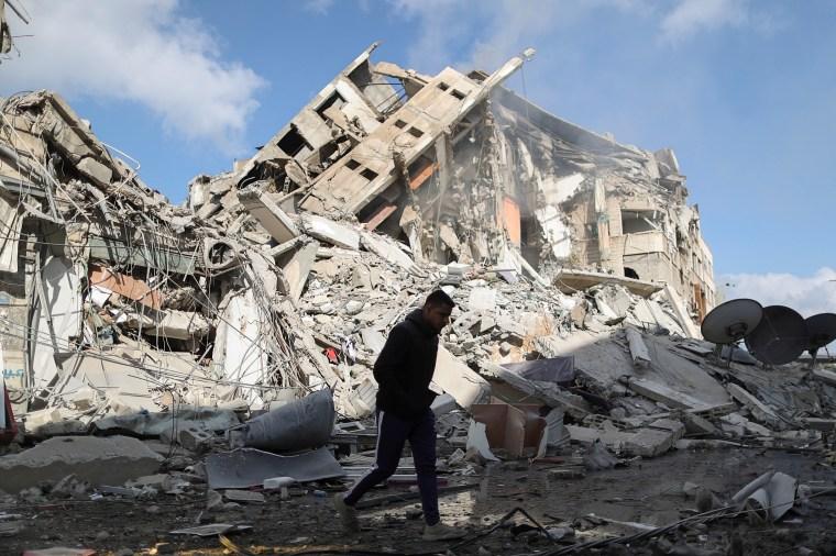 Un palestino pasa junto a los restos de un edificio destruido por los ataques aéreos israelíes en Gaza