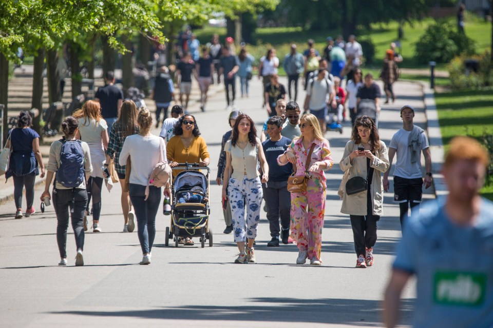 People take a Saturday stroll in Victoria Park, east London