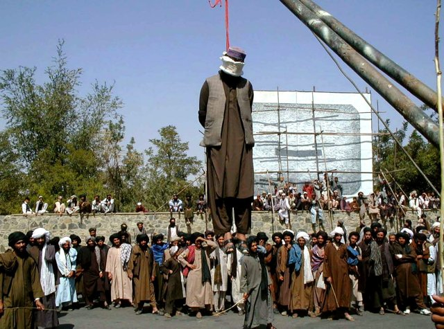 Hundreds of Afghan people gather round a man hanged by the Taliban in 2000