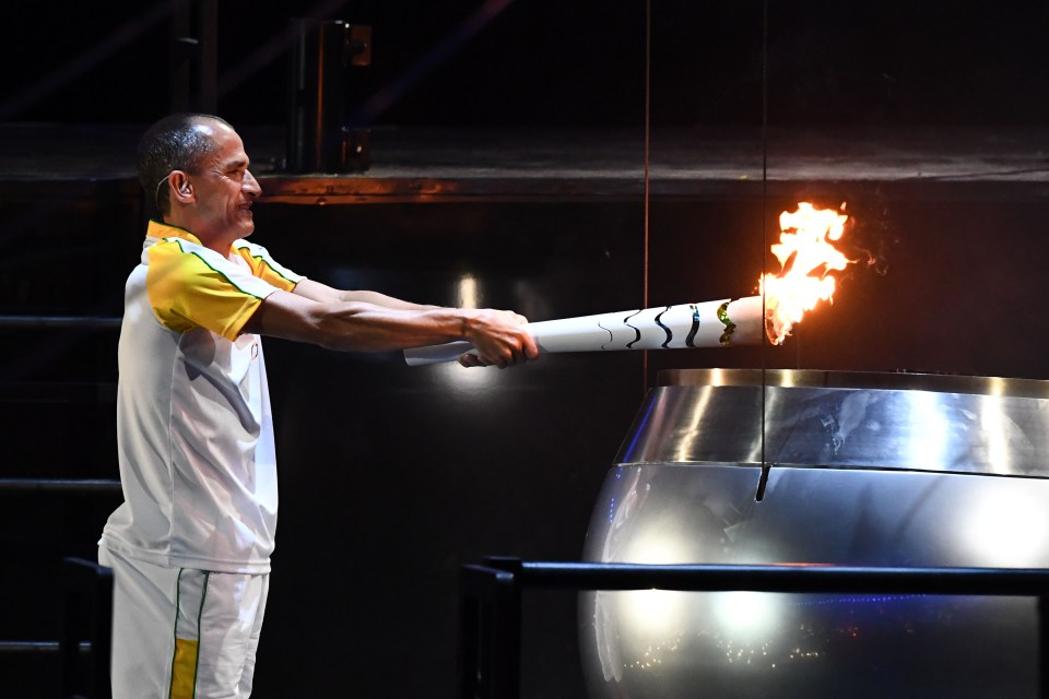 Former Brazilian athlete Vanderlei Cordeiro holds the Olympic torch to light the Olympic cauldron ahead of Rio 2016 Olympics opening ceremony