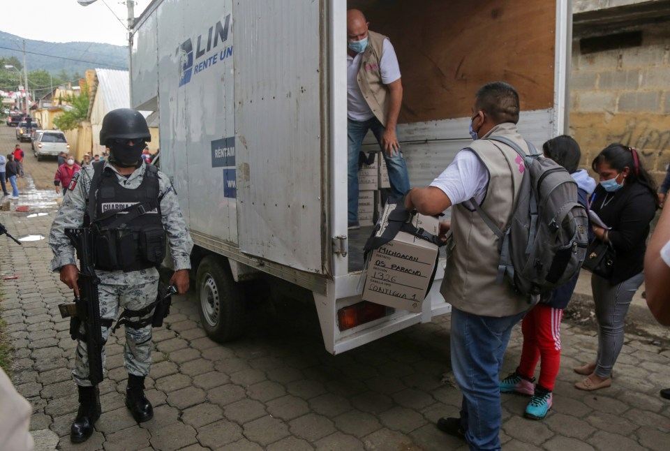 A soldier look on as vehicles arrive carrying voting booths and electoral boxes ahead of midterm elections in Nahuatzen, Mexico