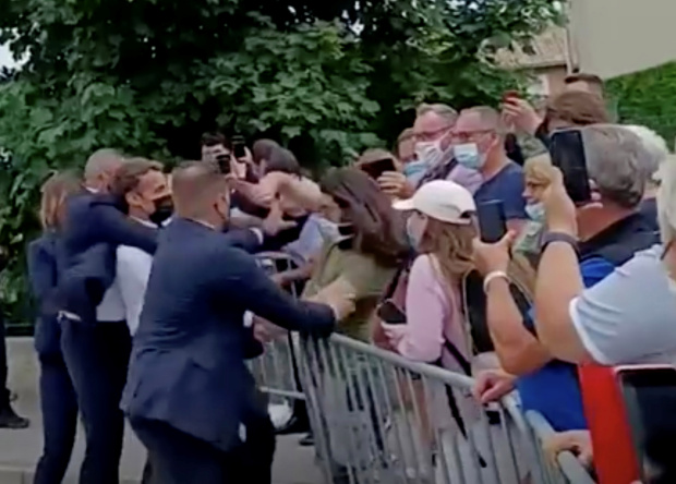 Security immediately pulled the French president off the fence