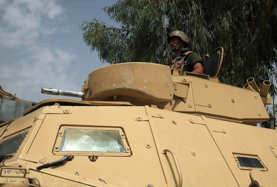 An Afghan soldier stands on a military vehicle as the Taliban encircles the city of Kandahar